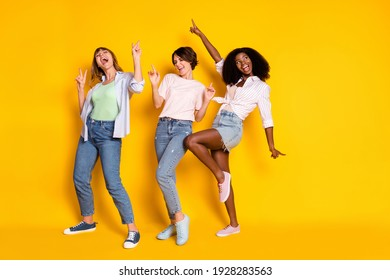 Full size photo of nice optimistic three ladies dance look empty space wear white shirt jeans isolated on yellow background