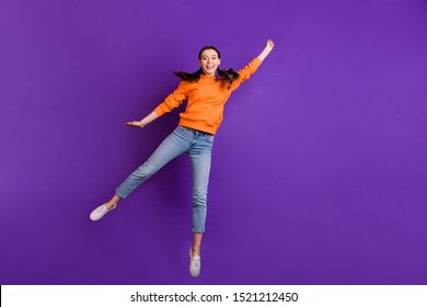 Full size photo of positive cheerful teen girl hold hand jump catch her flying parasol on windy weather wear orange sporty outfit jeans white sneakers isolated over violet purple color background