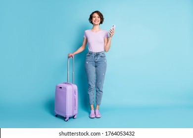 Full size photo of positive cheerful girl tourist hold baggage use smartphone booking taxi hotel wear lilac violet t-shirt denim jeans isolated blue color background - Shutterstock ID 1764053432