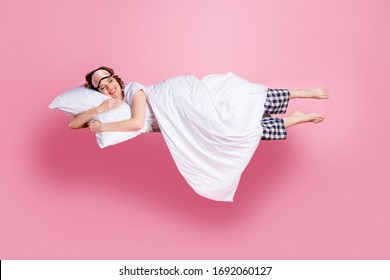 Full size photo of pretty cheerful lady satisfied morning nap lying bed hug pillow covered blanket wear mask white t-shirt plaid pajama pants barefoot isolated pink color background