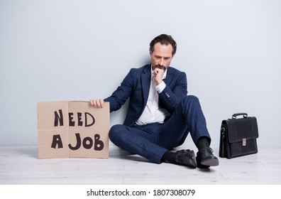 Full size photo of upset minded loser fired worker mature guy jobless man hold carton placard need work sit floor briefcase search office place wear suit shoes isolated grey background