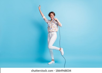 Full size photo of young attractive woman happy excited enjoy party sing song microphone isolated over blue color background
