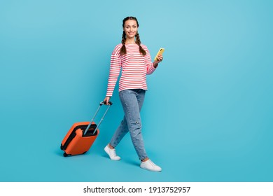 Full size photo of young girl happy smile go walk baggage trip use cell wear casual outfit isolated over blue color background