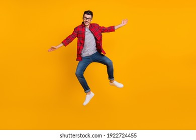 Full size photo of young happy excited smiling positive man in glasses jumping isolated on yellow color background
