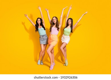 Full size photo of young happy smiling excited funky funny girls rising hands up isolated on yellow color background