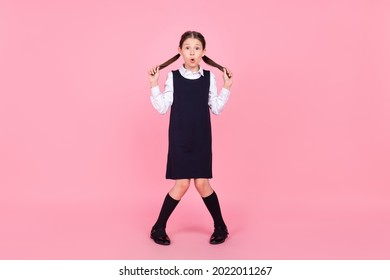 Full size photo of young school girl amazed shocked surprised shy isolated over pink color background