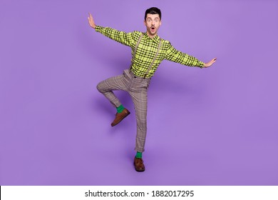 Full size photo of young shocked amazed surprised man dancing hold hands like wings isolated on violet color background