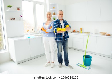 Full size portrait of attractive cleanly neat cheerful stylish couple of senior in colorful protective gloves standing with crossed arms after cleaning, looking at camera, having mop, bucket
