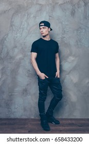 Full size portrait of attractive young man in cap and black cool outfit is on the grey background, his hands are in pockets, he looks away