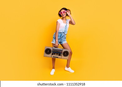 Full size portrait of cheerful positive girl in eyewear jeans overall holding boom box in hand going to make party isolated on yellow background. Music lover fan concept