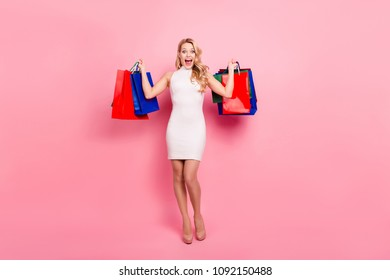 Full size portrait of crazy funny girl having colorful packets in raised arms yelling with wide open mouth isolated on pink background
