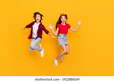 Full size portrait of two excited persons enjoy jumping open mouth isolated on yellow color background