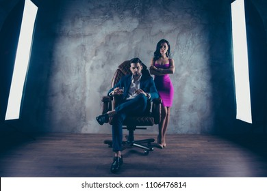Full size portrait of virile harsh boss in formal wear sitting in leather chair holding glass with cognac cigar in hands, charming bitch standing near with folded arms over dark grey background