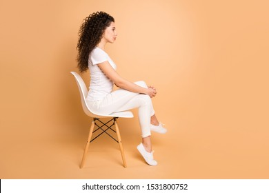 Full size profile photo of amazing lady sitting comfy chair looking strict to empty space not smiling wear casual clothes isolated beige pastel color background