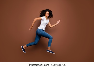 Full size profile photo of amazing dark skin lady jumping high sports competitions rushing finish line winner mood wear casual white t-shirt jeans isolated brown color background