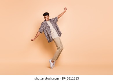 Full size profile photo of brunet optimistic guy dance wear modern shirt trousers sneakers isolated on beige color background - Shutterstock ID 1943811613