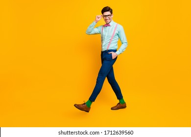 Full size profile photo of cool stylish guy boyfriend walk down street date girlfriend wear specs shirt bow tie suspenders trousers shoes isolated bright yellow color background