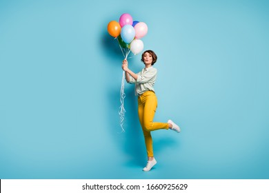 Full size profile photo of funny lady surprise birthday party hold many air balloons playful weekend mood wear casual green shirt yellow pants footwear isolated blue color background