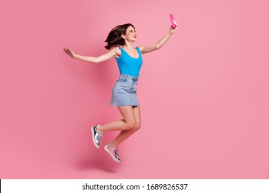 Full size profile photo of funny crazy lady jump high hold telephone making selfies speak talk skype wear casual blue tank-top denim short skirt shiny shoes isolated pink color background