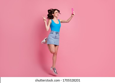 Full size profile photo of funny crazy lady jump high hold telephone making selfies show v-sign symbol wear blue tank-top denim short skirt shiny shoes isolated pink color background