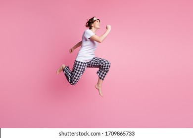 Full size profile photo of funny lady jump high up rush sales shopping didn't change sleep clothes wear sleep mask white t-shirt plaid pajama pants barefoot isolated pink color background