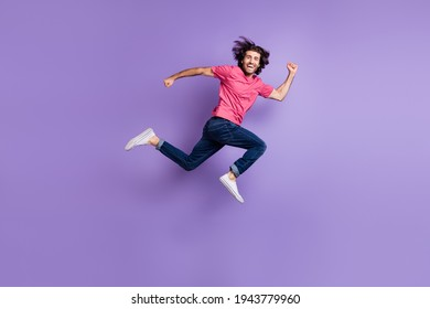 Full size profile photo of optimistic nice brunet guy jump wear pink t-shirt jeans isolated on violet background
