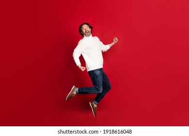 Full size profile portrait of astonished guy jumping open mouth celebrate isolated on red color background