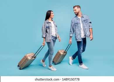 Full size profile side photo of two sweethearts carrying baggage seeing off wearing denim jeans jackets isolated over blue background