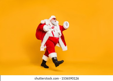 Full size profile side photo of funky fat santa claus with huge abdomen hold gift wish bag go walk travel around world on christmas night eve wear x-mas hat suspenders isolated bright color background