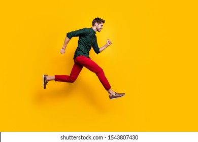 Full size profile side photo of positive cheerful guy jump run fast want hurry to sales discounts wear casual style clothes sneakers isolated over yellow color background