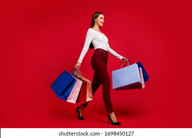 Full size profile side photo stunning pretty girl shopping center client buy off-sales go walk step hold bags wear white plaid pants stilettos isolated bright shine color background