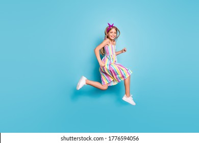 Full size profile side photo of cheerful kid girl jump run after summer season discount wear stylish trendy purple headband sneakers isolated over blue color background