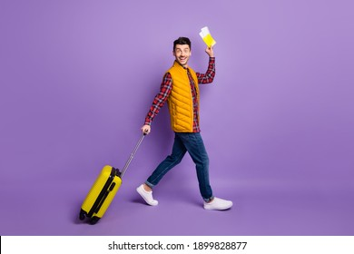 Full size profile side photo of brunette trendy man wear casual outfit hold baggage tickets travel isolated on violet color background
