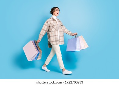 Full size profile side photo of young girl happy amazed sale hold bags go shopping look empty space isolated over blue color background