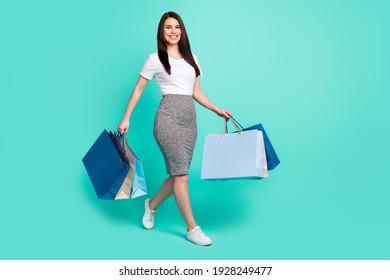 Full size profile side photo of young woman happy smile go walk shopper bags black friday isolated over turquoise color background