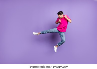 Full size profile side photo of young happy excited man look copyspace doing karate jumping isolated on violet color background