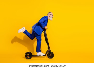 Full size profile side photo of happy excited crazy mature man look copyspace riding scooter isolated on yellow color background
