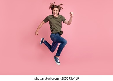 Full size profile side photo of young guy happy positive smile go walk run hurry jump isolated over pastel color background