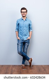 Full size vertical portrait of cheerful brunet young man in casual stylish wear. He looks at camera on lifgt background