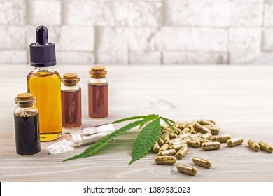 Full spectrum Cannabidiol CBD oils, capsules and crystals isolate on wooden backdrop with hemp leaf