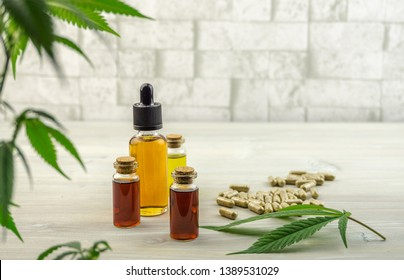 Full Spectrum Cannabis CBD and THC oils and pills on wooden backdrop