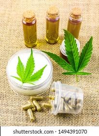 Full spectrum CBD and THC cannabis oils, pills and cbd lotion on hemp cloth