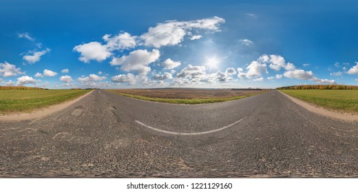 Full spherical seamless panorama 360 degrees angle view on no traffic asphalt road among fields in sunny day with awesome clouds. 360 panorama in equirectangular equidistant projection, VR AR content