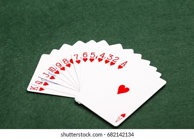A full suit of thirteen Hearts playing-cards laid out in a fan shape on a green baize background