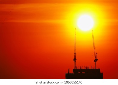 Full sunset silhouette construction building tower crane