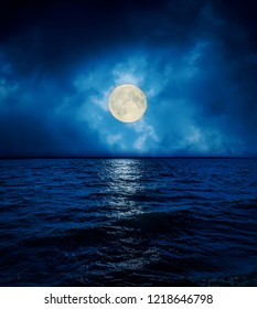full super moon in dramatic clouds over dark water