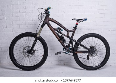 Full suspension mountain bike on a brick wall background. Active lifestyle.