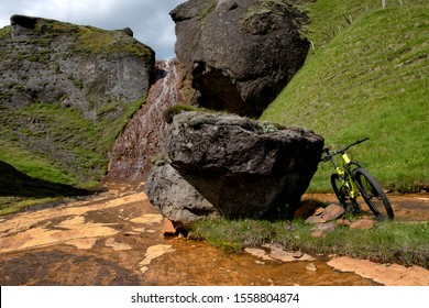 Full suspension mountain bike on a trail in Iceland, standing against að big rock with a small creek and waterfall to the side, copy space to the left.