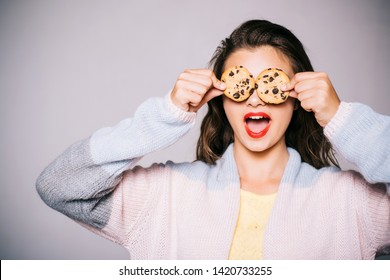 Full of sweet chocolate flavors. Cute girl having fun with cookies. Pretty girl covering eyes with cookies. Bakery style chocolate chip cookie recipe. Bakery shop. Following a cooking recipe.