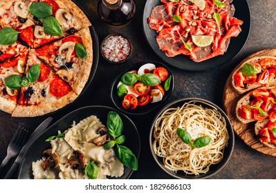 Full table of italian meals on plates Pizza, pasta, ravioli, carpaccio. caprese salad and tomato bruschetta on black background. Top view - Shutterstock ID 1829686103